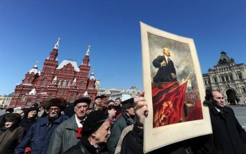 Russian Communist supporters carry a portrait of party founder Vladimir Lenin at his mausoleum on Red Square in Moscow on April 22, 2009, while paying their respect on the 138th anniversary of his birth. | NATALIA KOLESNIKOVA/AFP/Getty Images